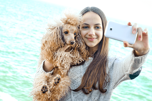 woman taking selfie with curly haired dog