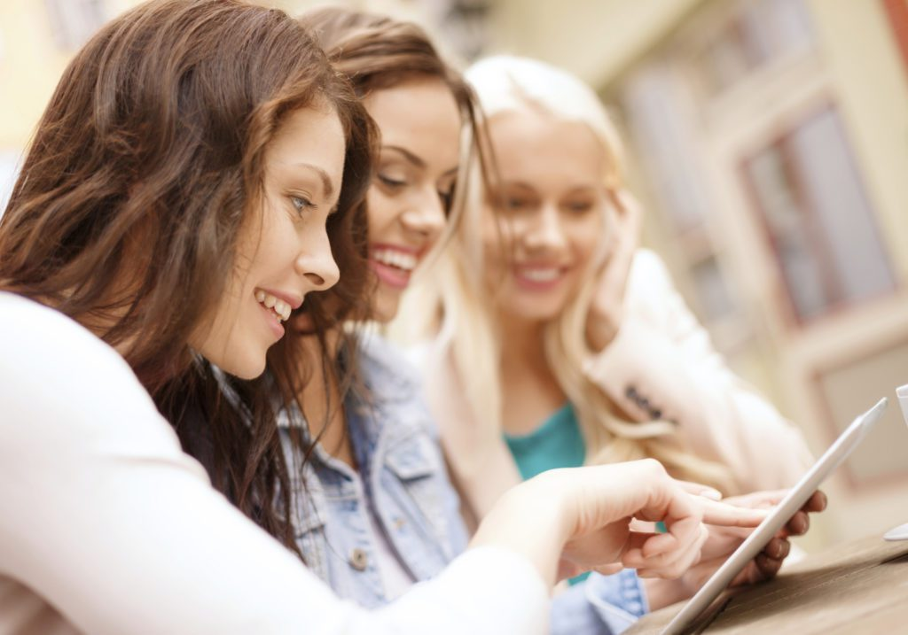 three women looking at tablet screen