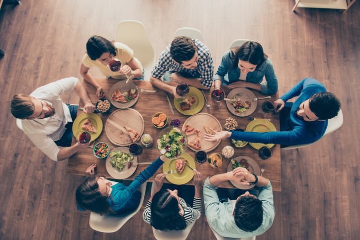 Friendship and communication concept. Top view of group of eight happy friends having nice food and drinks, enjoying the party and communication