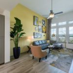 living room with yellow wall couch and chair with ceiling fan
