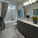 bathroom with white countertops and gray cabinets