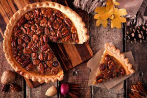 Pecan pie with slice removed, table scene over wood