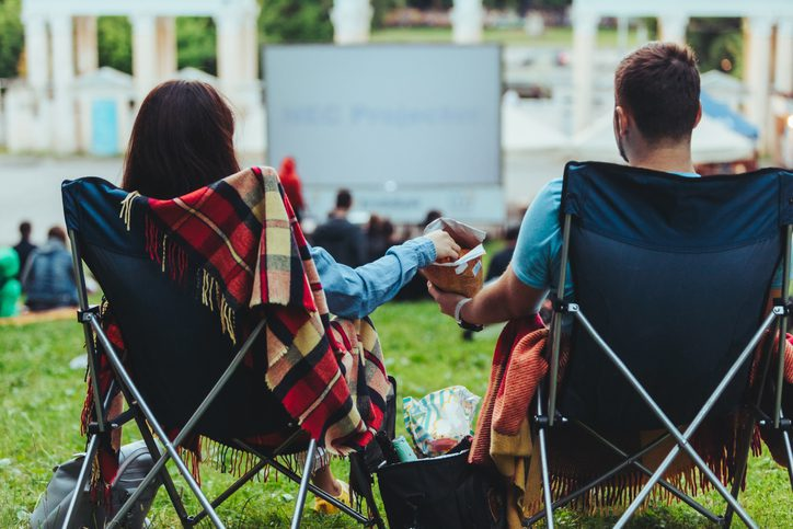 couple sitting in camp-chairs in city park looking movie outdoors at open air cinema