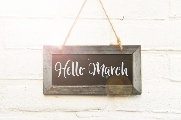 Hello March hand lettering on hanging sign board in spring sunlight