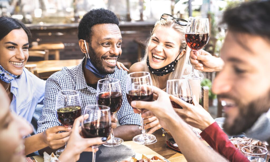 Friends toasting red wine at outdoor restaurant bar